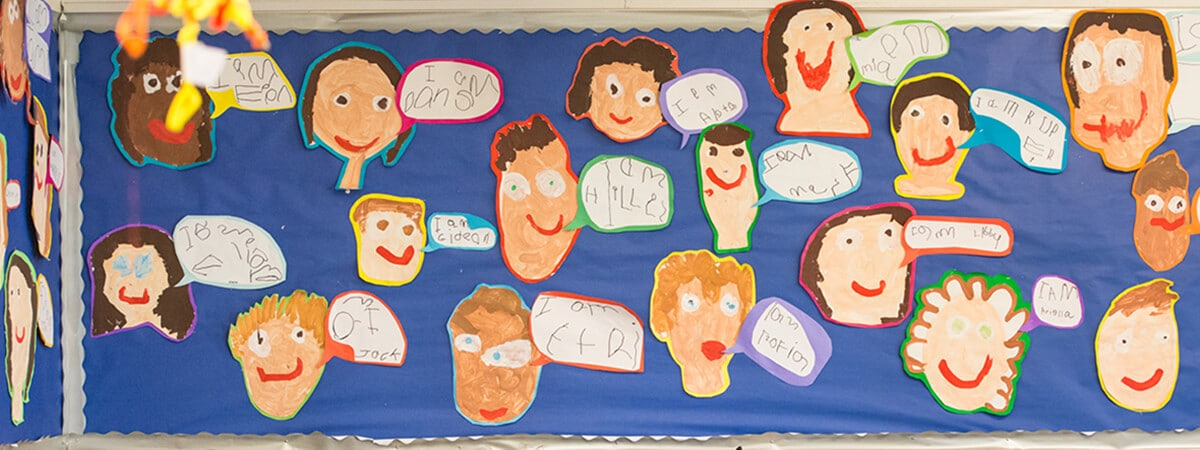 Self-portraits by pupils displayed on a classroom wall