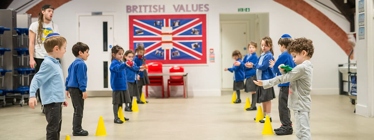Children lined up below the British flag in Sacks Morasha Jewish Primary School