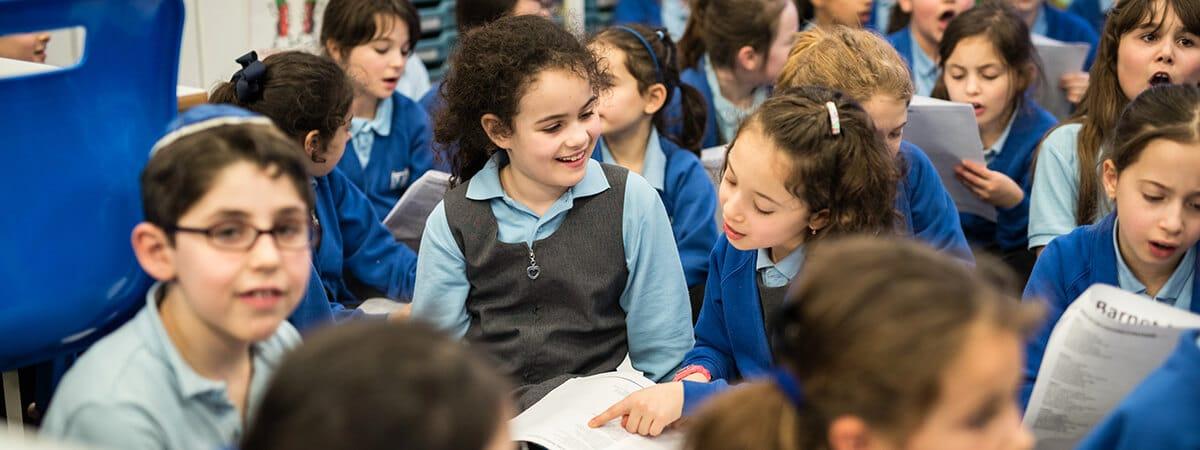Pupils sharing a music book in a Sacks Morasha choir rehearsal