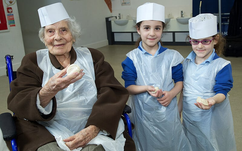 Two Sacks Morasha pupils with a resident of Rubens House, enjoying Matzah baking